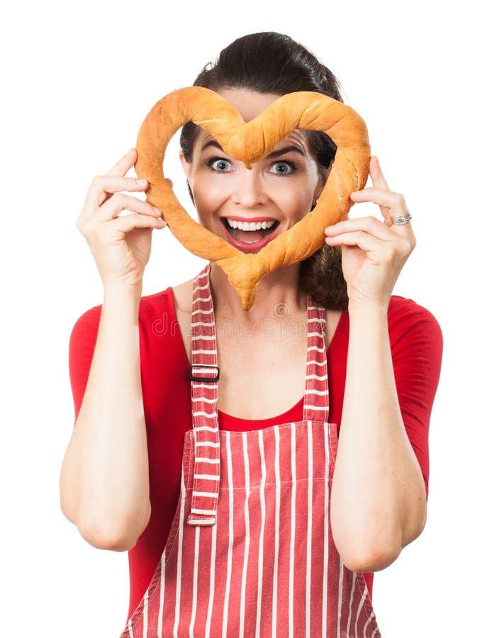 Happy woman looking through bread love heart
