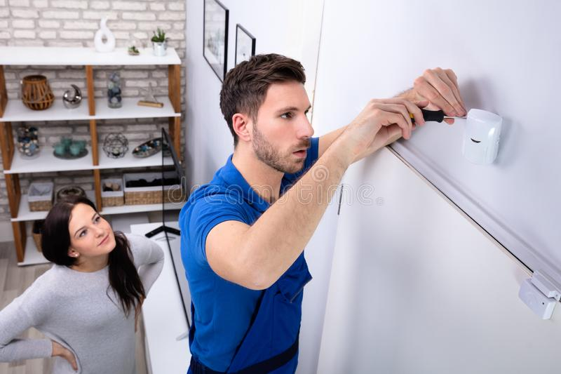 Electrician Installing Security System Motion Detector On Wall. Happy Woman Looking At Electrician Installing Security System Motion Detector On Wall stock image