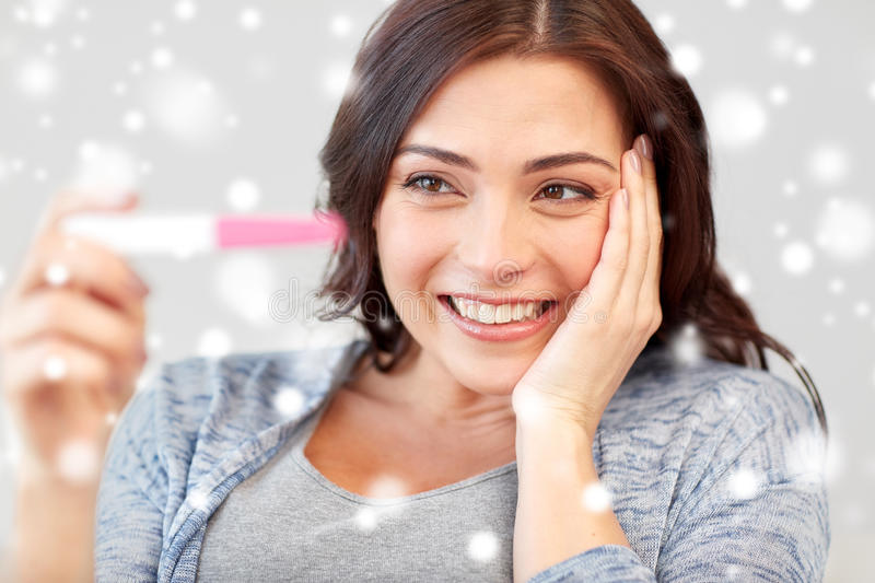 Happy woman looking at home pregnancy test royalty free stock photography