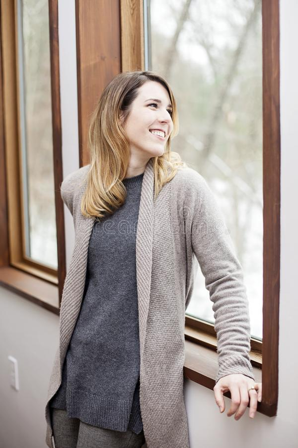 Happy woman looking out window in winter. A smiling young woman looking out window at sky at home in winter royalty free stock photos