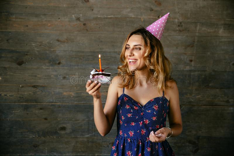 Happy woman looking at piece of chocolate cake with candle stock photos