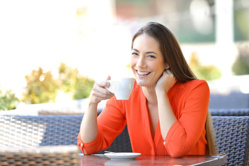 Happy woman looking at you holding coffee mug in a bar royalty free stock photos
