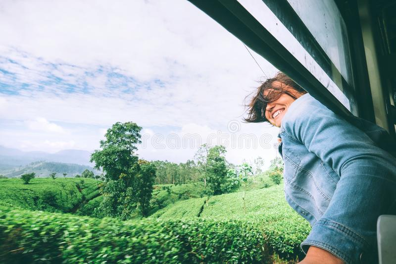 Happy woman looks out from train window during traveling on most stock images