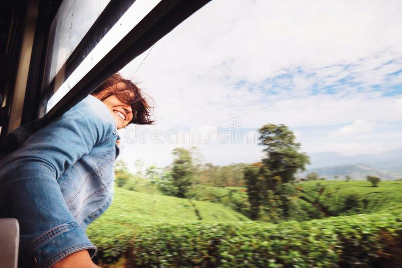 Happy woman looks out from train window during traveling on most stock image