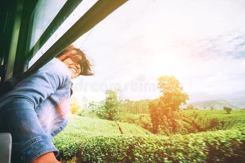 Happy woman looks out from train window during traveling on most stock photo