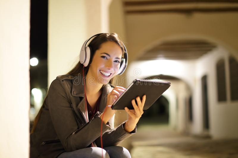 Happy woman looks at you listening tablet content stock photo