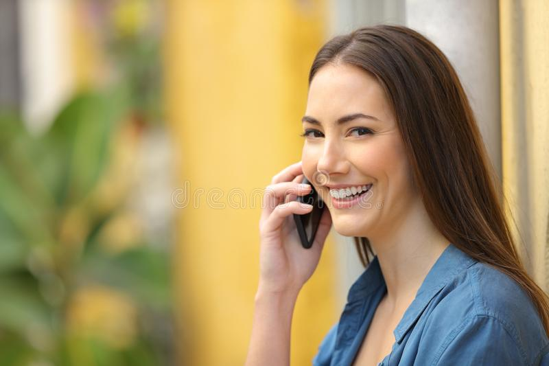 Happy woman looks at you talking on phone in the street. Happy woman looks at you talking on smart phone in a colorful street stock images