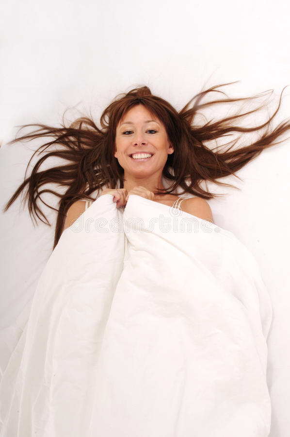 Happy woman lying in bed. Woman lying in bed smiling with a lot of copy-space on the white blanket stock photos