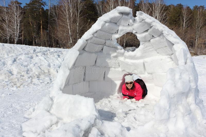 Happy woman lying at the entrance in unfinished an igloo. Happy woman in a red jacket lying at the entrance in unfinished an igloo on a snowy glade stock photography