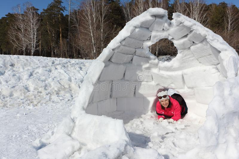 Happy woman lying at the entrance in unfinished an igloo. Happy woman in a red jacket lying at the entrance in unfinished an igloo on a snowy glade stock photo