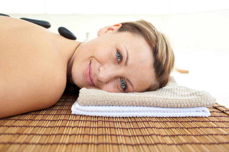 Happy woman lying on massage table with hot stones royalty free stock images