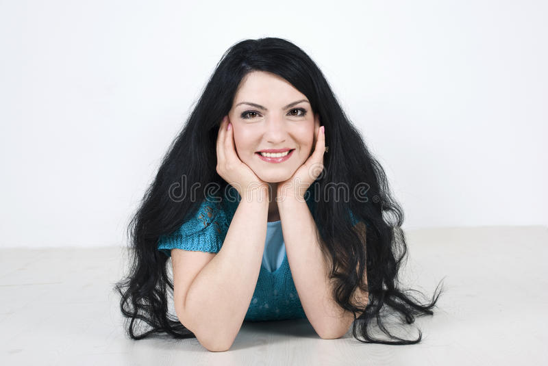 Happy woman lying on wooden floor royalty free stock photography