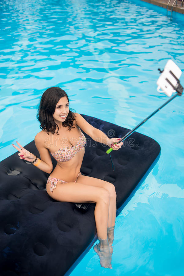 Happy woman makes selfie photo on the phone with selfie stick on mattress in pool. View from above royalty free stock photo