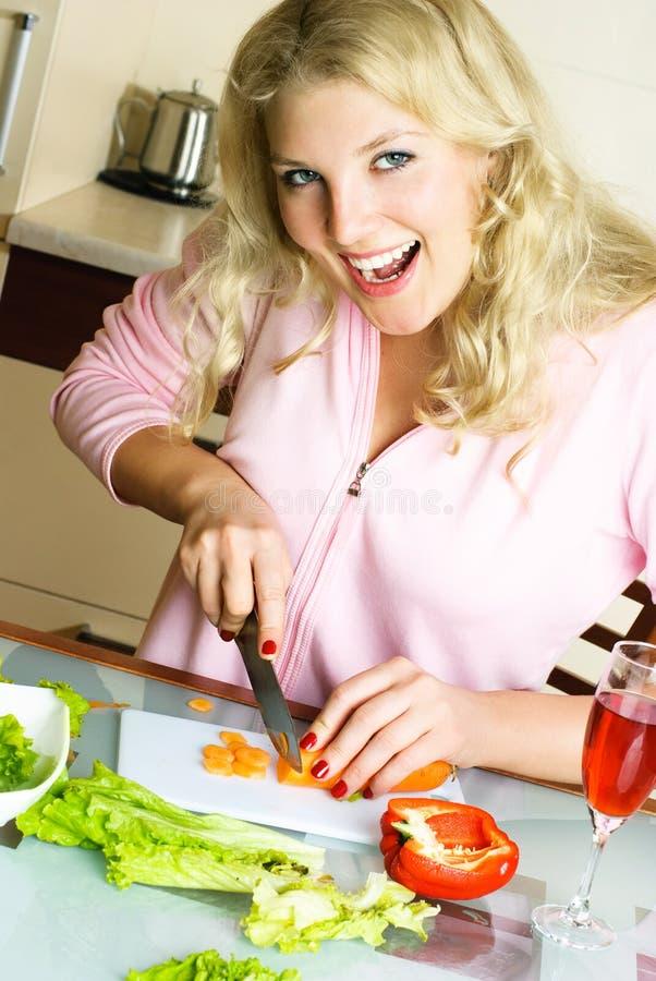 Happy woman making salad royalty free stock photography