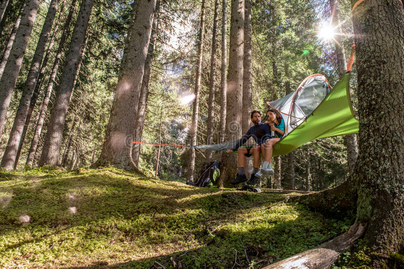 Happy woman man couple relaxing in hanging tent camping in forest woods during sunny day.Group of friends people summer stock photos