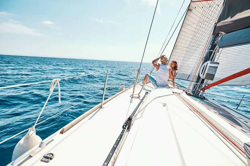 Happy woman with man relaxing on sailboat deck. Young happy woman with man relaxing on sailboat deck on vacation royalty free stock images