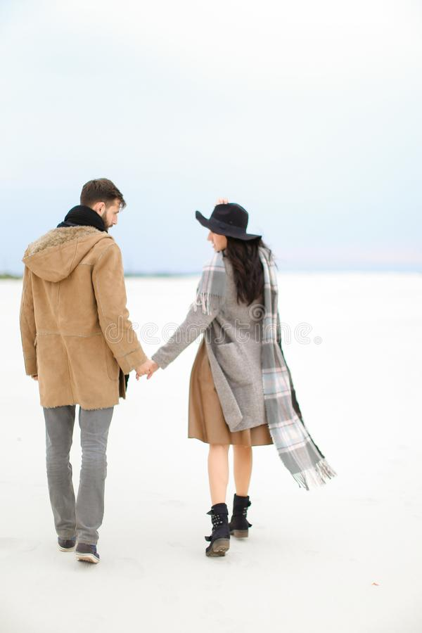 Happy woman and man walking on snow and holding hands, wearing coat, grey scarf and hat. Happy women and men walking on snow and holding hands, wearing coat royalty free stock image