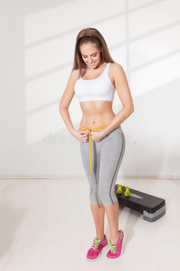 Happy woman measuring her waistline. With a measuring tape royalty free stock images