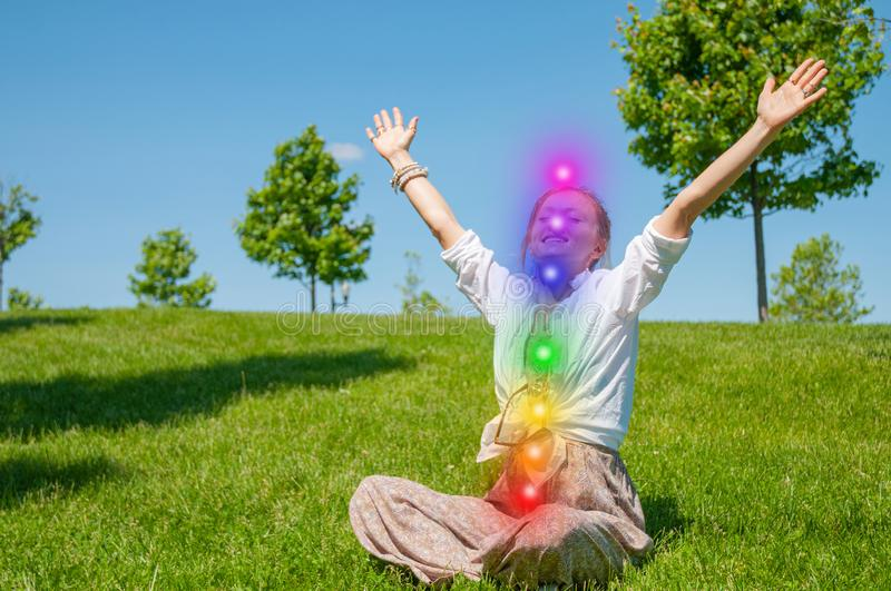 Happy woman is meditating in the lotus pose with glowing seven chakras on grass. Woman is practicing yoga on the park. Kundalini meditation stock photos