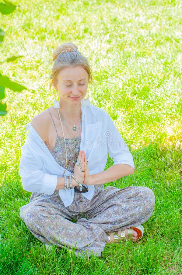 Happy woman is meditating sitting in Lotus pose on grass. Beautiful boho style woman with accessories enjoying sunny day in park royalty free stock photos