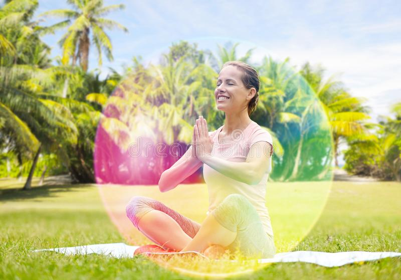 Happy woman meditating in summer park over aura royalty free stock photography
