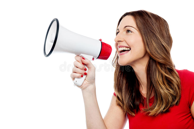 Happy woman with mega phone. Young woman holding megaphone over white stock photography