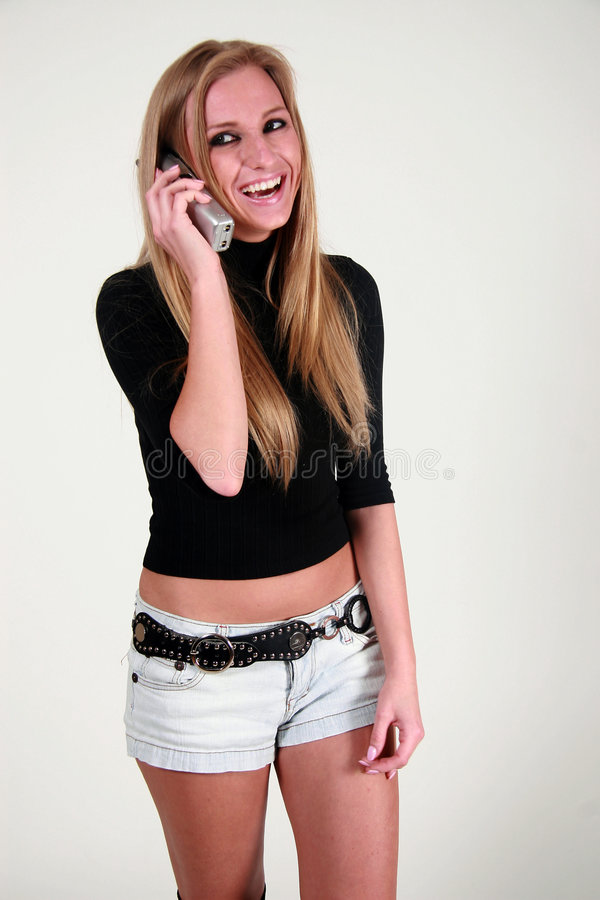 Happy woman with mobile. Happy young blond woman with mobile telephone; studio background royalty free stock images