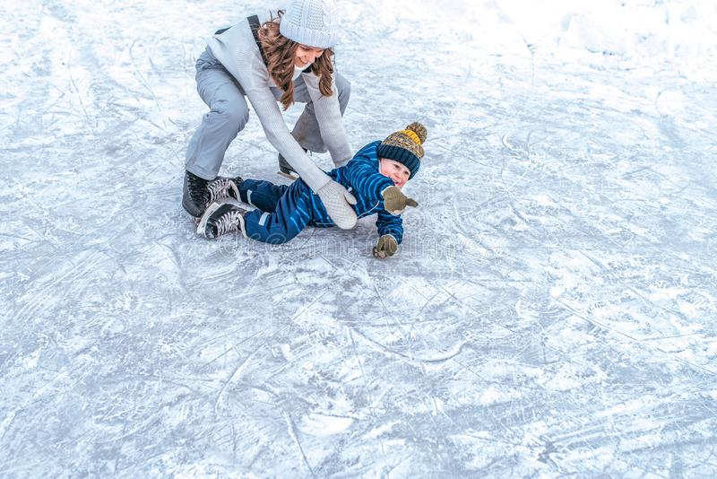 A happy woman mom raises her son, little bitch 3-5 years old. In winter in city on a public skating rink. Joy is game. A happy women mom raises her son, little royalty free stock images