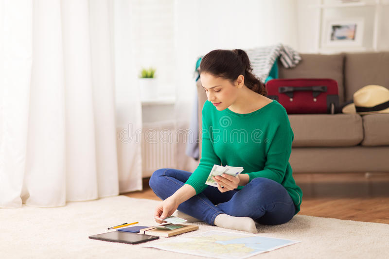 Happy woman with money and travel map at home royalty free stock images