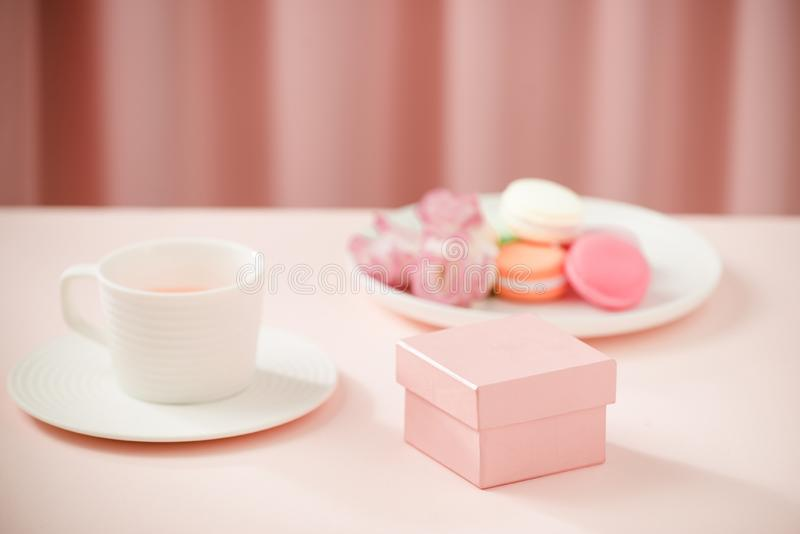 Happy woman/mother`s Day image of a coffee or tea cup and lisianthus flower with macaroon and gifts beside on drapes of pink. Happy woman/mother`s Day image of stock images