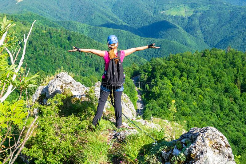 Happy woman on the mountain ridge called `Pietrele Negre` in Apuseni mountains, Romania, enjoying the view from a via ferrata. Happy woman on the mountain ridge stock images