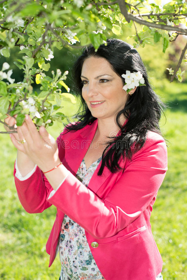 Happy woman in nature. Admire apple flower in spring landscape royalty free stock image