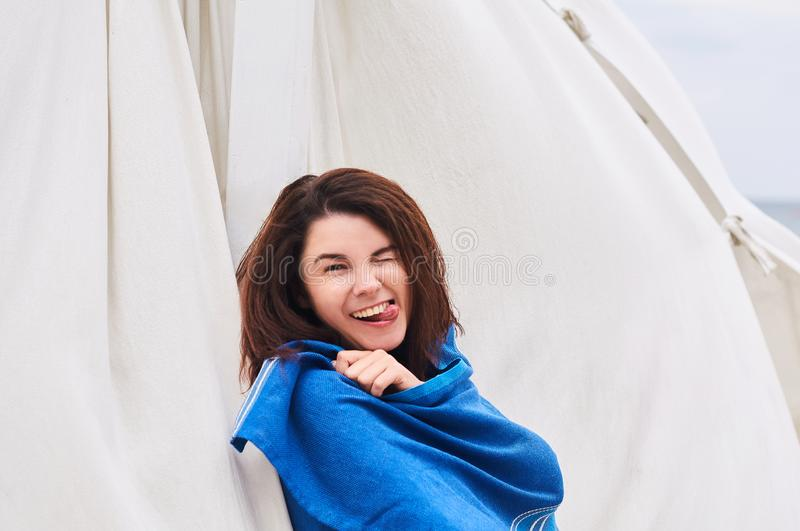 Young woman during camping travel trip stands on the beach snuggled in throw blanket or plaid inspired and laughed royalty free stock photo