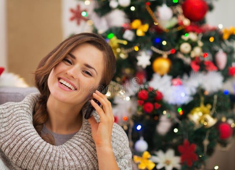 Happy woman near Christmas tree making phone call royalty free stock photography