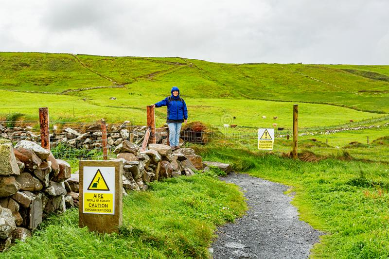 Happy woman next to a fence on a rainy day in the coastal walk route from Doolin to the Cliffs of Moher. Geosites and geopark, Wild Atlantic Way, spring day in stock image
