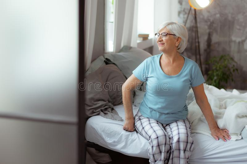 Good-looking woman looking into windows while sitting on the bed. royalty free stock photography