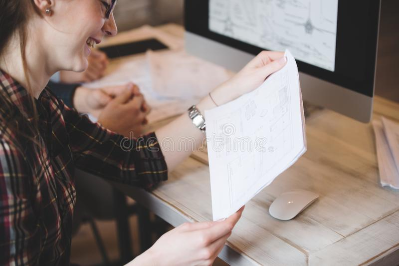 Happy woman in office looking at blueprint royalty free stock photos