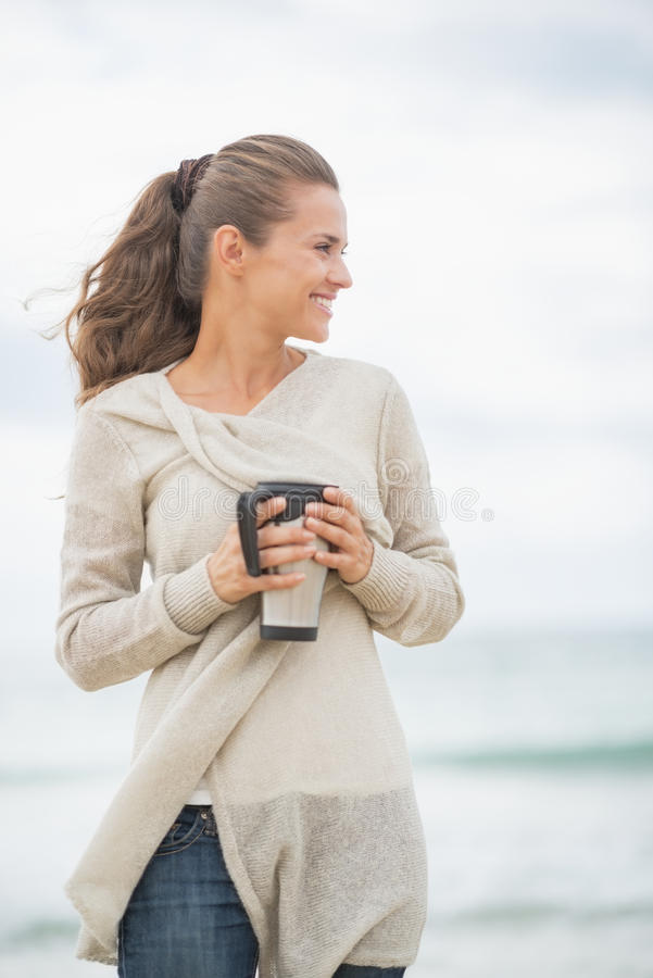 Free Happy Woman On Cold Beach With Cup Of Hot Beverage Royalty Free Stock Image - 39498676