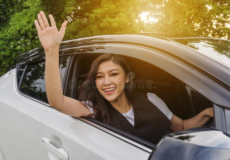 Happy woman open window of a car and raising her hand royalty free stock photo