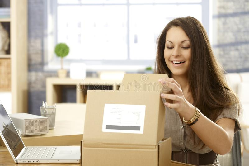 Happy woman opening postal packet. Young woman sitting at table, opening postal packet, smiling happy royalty free stock images