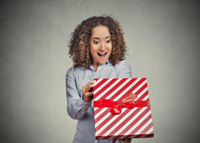 Happy woman opening unwrapping red birthday gift box stock image