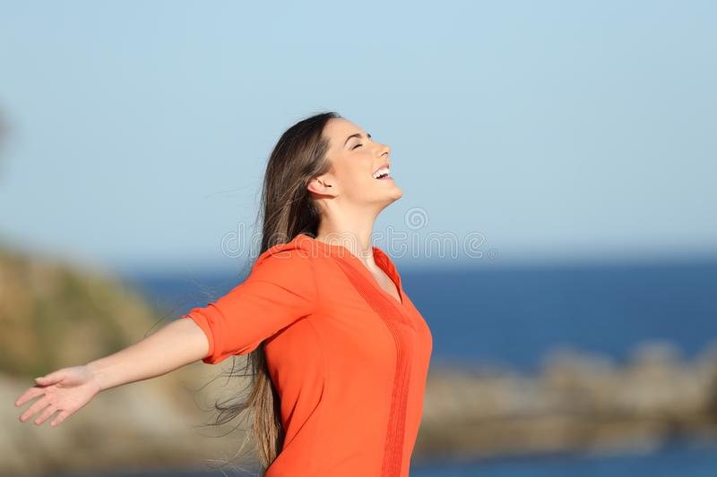 Happy woman in orange breathing fresh air in the coast royalty free stock photo