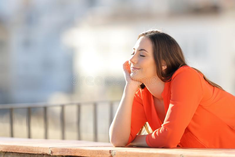 Happy woman in orange meditating in a balcony royalty free stock image