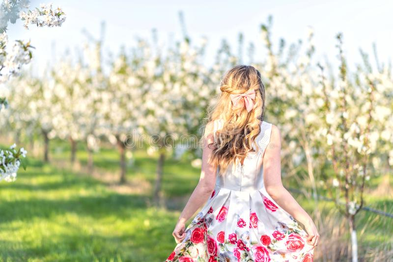 Happy Woman in an orchard at springtime. Enjoying sunny warm day. Retro style dress. Blooming blossom cherry trees stock photos