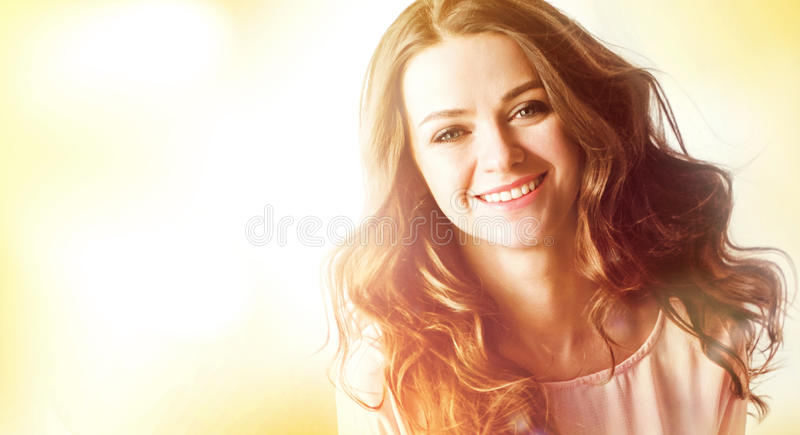 Happy woman outdoors. Portrait of the beautiful girl close-up, the wind fluttering hair. stock photography
