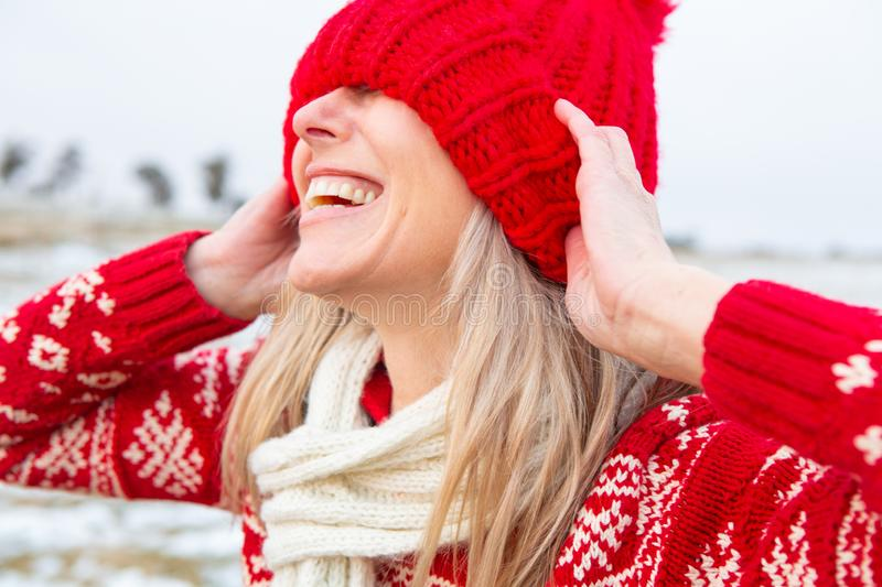 Happy woman outdoors pulling beanie over eyes royalty free stock image