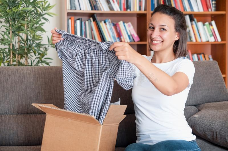 Happy woman after package delivery at home. Cheerful woman after online shopping shipping royalty free stock images