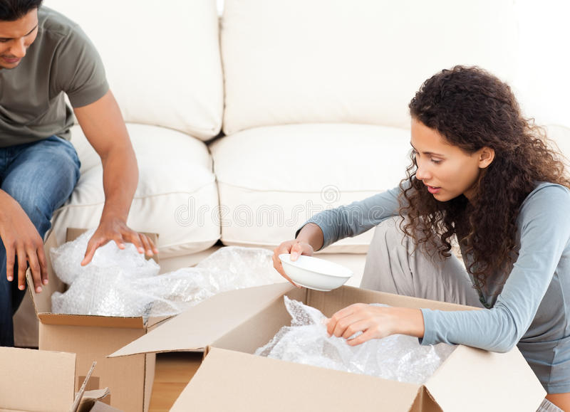 Happy woman packing glasses with her husband stock photography