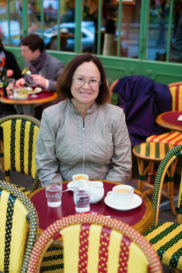 Happy woman in Paris drinking coffee. Happy middle aged woman in Paris drinking coffee royalty free stock images