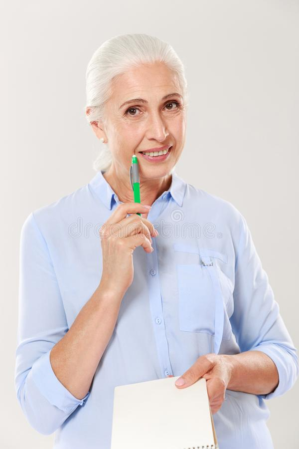 Happy woman with pen and notebook looking camera and smiling stock photo